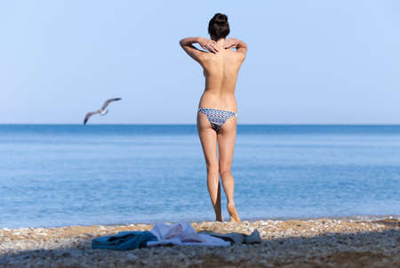 Morning on beach. Young woman in swimming trunks standing on beach and observing flight of seagull in morning time Stock Photo