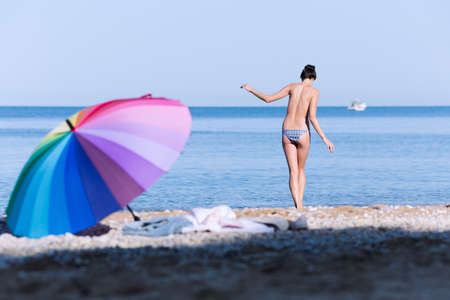 Beach still life from rainbow umbrella and ladies clothes. Seashore with swimmer girl entering in sea water in morning time