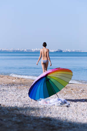 Beach still life from rainbow umbrella and ladies clothes. Seashore with tall girl walking along waters edge