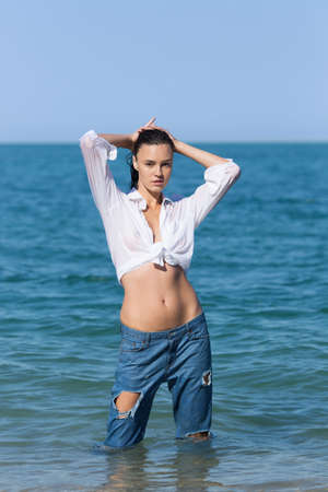 Wet young woman in torn jeans and shirt tied in knot posing in sea. Attractive girl in white shirt tied in knot and ripped jeans stands in sea water with arms raised