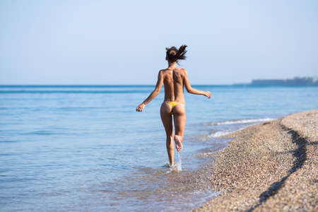 Female person in yellow swimming trunks running along seashore, rear view. Barefoot topless girl moving on waters edge