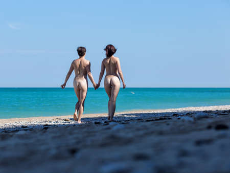 Homosexual couple at the sea. Two female persons walking holding hands along seashore in morning time, rear view