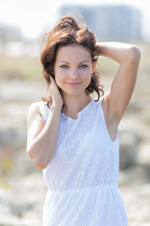 Waist up portrait of cute girl in white outdoors. Curly young woman in white sleeveless dress poses with hands on head. She looks at camera and smiles Stok Fotoğraf