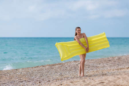 Young woman with yellow pool raft on pebble beach. Female person hides her nudity behind  inflatable raft looking at camera