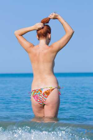 Topless ginger girl in sea, rear view. Red haired young woman in swimming trunks stands knee-deep in seawater and adjusts her hairstyle