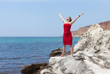 Girl on wild rocky seashore. Attractive female person in red sundress barefoot stands on rock with arms raised Фото со стока