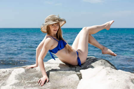 Portrait of white-skin girl in beach hat on wild seashore. Attractive female person in blue swimsuit and broad-brim hat reclines on rock leaning on hands and waving legs 写真素材