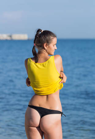 Girl undresses against sea. Young female person in black thongs takes off yellow tank top looking away