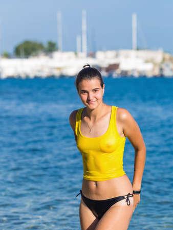 Giovane donna dai capelli scura che posa in canottiera bagnata alla spiaggia della città. Ritratto di donna castana attraente in abbigliamento trasparente bagnato contro il mare