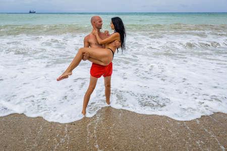 Couple attrayant à la mer en été jour couvert. L'homme en maillot de bain rouge tient sa femme en bikini contre la mer orageuse Banque d'images