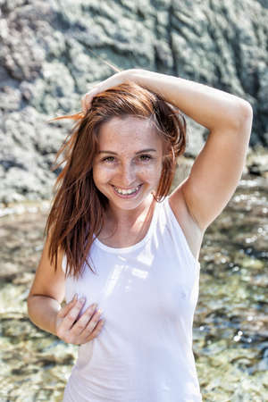 Portrait of smiling girl in white tank top against rocky seashore. Female person posing with hand on head, she looking at camera laughing