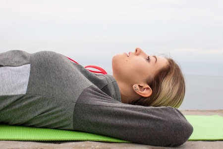 Female person resting after workout outdoors. Teen girl in sportswear lies with her hands behind her head on back on sleeping pad and looks up