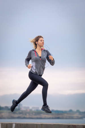 Jogging. Female person running along waterfront. Teen girl in sportswear jogging outdoors in overcast day