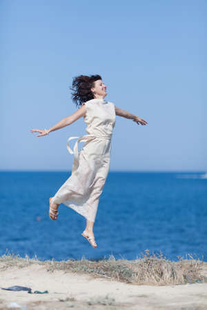 Jumping girl. Middle aged woman in white long dress hopping against sea with arms outstretched