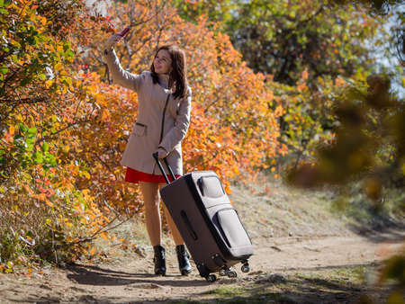 Young woman with the luggage on country road in the forest. Female person in short red dress and coat taking selfies against autumn trees
