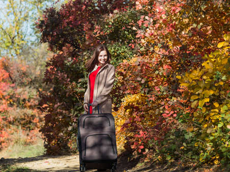 Young woman with the luggage on country road in the forest. Female person in red dress and coat walking along autumn trees