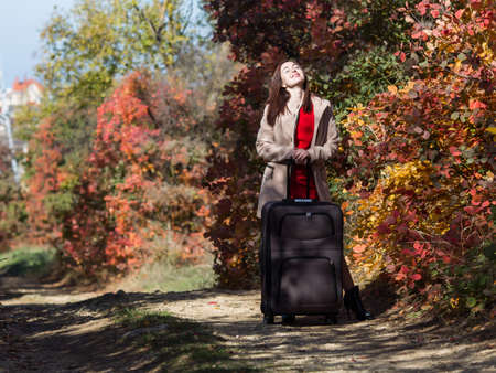 Young woman with rolling suitcase on country road in the forest. Female person in red dress and coat walking along autumn trees Stock Photo