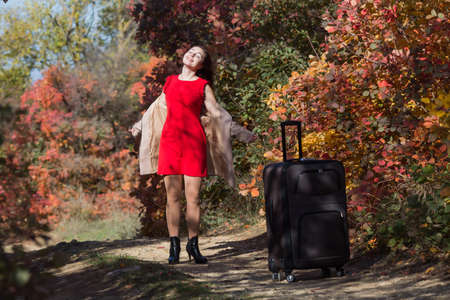 Young woman with the luggage on country road in the forest. Female person in short red dress and coat spinning arms outstretched and looking up Stock Photo