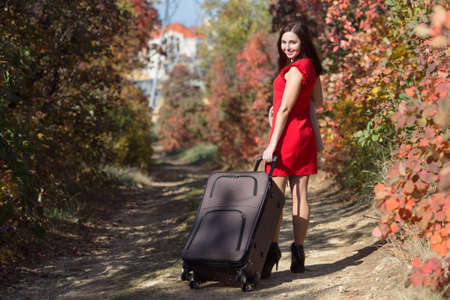 Young woman with rolling luggage on country road in the forest. Female person in red dress walking under autumn trees Stock Photo