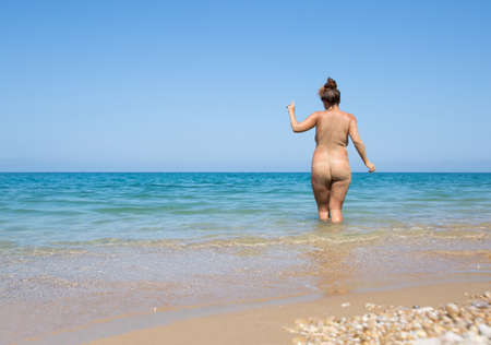 Naked female person resting at the sea. Young overweight woman entering in sea, rear view