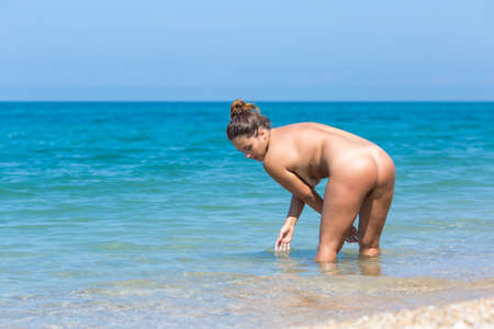 Female person resting at the sea. Naked young overweight woman entering in sea. She stands knee-deep in sea, bends and touches water Archivio Fotografico - 112404466
