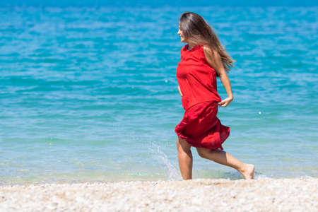 Long haired female person resting at the sea. Young woman in long red dress running along seashore Stockfoto
