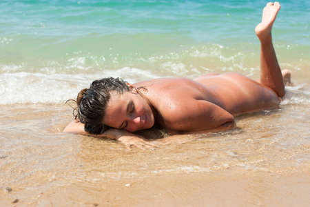 Female person resting on pebble-sandy beach. Naked young woman lying on front on wet sand in line of surf Stockfoto