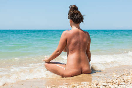 Female person resting on pebble-sandy beach. Naked young woman sits on wet sand in line of surf and looks on the sea