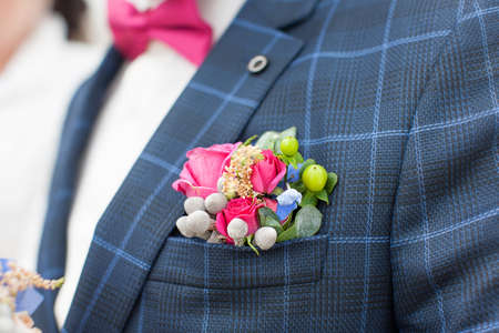 Boutonniere from fresh flowers. Nice wedding accessory on the plaid suit of the groom during the wedding ceremony 写真素材
