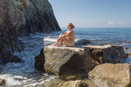 Young overweight woman resting at the sea. Naked young woman sunbathing in secluded place among coastal rocks