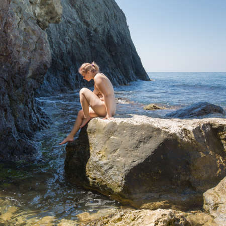 Young overweight woman resting at the sea. Naked young woman climbs down from stone in sea among coastal rocks