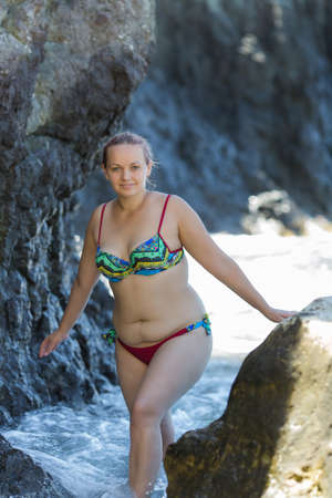 Young overweight woman resting at the sea. Young chubby woman in bikini comes out from sea among coastal rocks Фото со стока