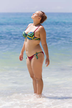 Overweight female person resting at the sea. Young chubby woman in bikini stands ankle-deep in water and sunbathing with eyes closed 스톡 콘텐츠