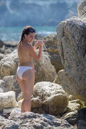 Chica en playa rocosa. Mujer joven se quita la parte superior del bikini y se seca entre piedras costeras