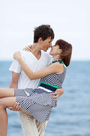 Jeune couple contre mer par temps couvert. Mec mince portant sa petite amie aux cheveux noirs. Ils s'embrassent et se regardent dans les yeux