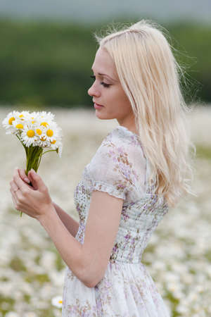 Portrait of slim girl with bouquet of chamomile in her hands. Young blond woman posing in summer dress with short sleeves against a chamomile field