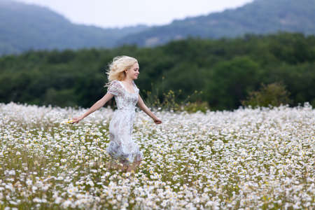 Slim girl in light dress jumping in chamomile field. Attractive young woman running along camomile field in overcast day