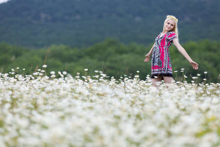 Portrait of slim girl in light dress in chamomile field. Attractive young woman in chamomile wreath posing with arms outstretched in overcast day
