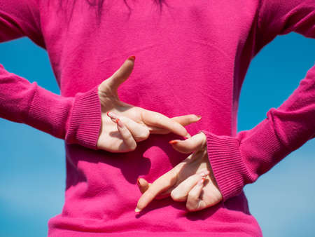 Hands of female person in pink blouse. Girl crossed her fingers and hiding hands behind back