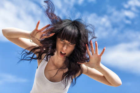 Portrait of dark haired female with loose hair against sky. Attractive young woman in white tank top leaning over camera with arms raised and open mouth, low angle view