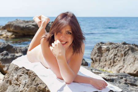 Young woman sunbathing on rocky seashore. Naked female person lying on front on white towel