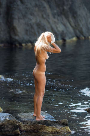 Tanned blond haired female person resting at secluded place of wild rocky seashore. Naked blonde woman standing on coastal stone. She collects her hair before bathing Imagens - 118563348