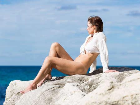 Persona di sesso femminile che riposa sulla spiaggia rocciosa selvaggia. Donna seminuda in camicia completamente sbottonata e annodata che prende il sole sulla roccia costiera. Si siede appoggiandosi sulle mani e piegando le ginocchia