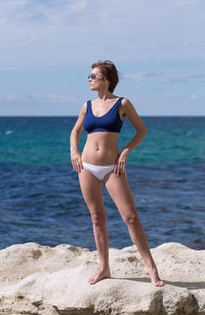 Portrait of barefoot thirty-nine-year-old woman against sea. Female person in sunglasses, sport bra and white panties posing with hands on hips on beach. She stands on white coastal rock and looking away
