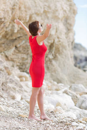 Female person posing among white rocks. Barefoot woman in red sleeveless dress and sunglasses stands with arms outstretched on pebble and looking up