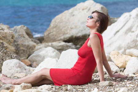 Female person resting on rocky seashore. Barefoot woman in red sleeveless dress and sunglasses sits leaning on hands on pebbles and looks up