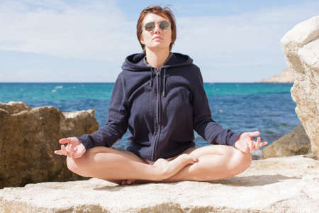 Female person relaxing on wild rocky seashore. Thirty-nine-year-old woman in sports jacket with hood and sunglasses doing yoga on coastal stone. She sits in half-lotus position against sea
