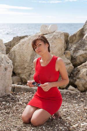Porträt der knienden Frau draußen. Attraktive weibliche Person in rotem, ärmellosem Kleid kniet auf Kieselsteinen, hält eine Sonnenbrille in den Händen und sieht die Kamera mit ernstem Gesicht an Standard-Bild