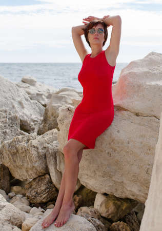 Portrait of thirty-nine-year-old barefoot woman on rocky beach. Attractive female person in round sunglasses and sleeveless red dress posing, leaning against a stone with crossed arms behind head Stock Photo