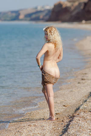 Female person posing on seashore. Blonde woman with scarf on her hips standing near waters edge Фото со стока